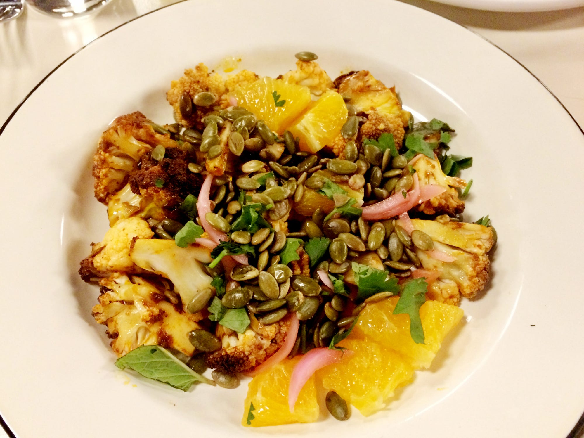 Roasted cauliflower with orange segments, pickled red onion and pepitas at Mop/Broom Mess Hall.