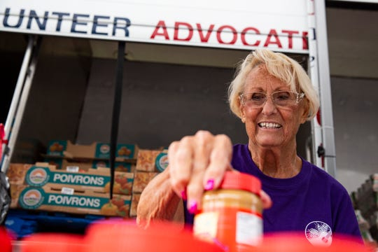Volunteer Isabel Garland arranges jars of creamy peanut butter for the Harry Chapin Mobile Food Pantry distribution moments before the start of the giveaway at East Naples Community Park on Tuesday, Nov. 27, 2018.