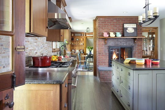 Sharon L. Sherman of Thyme & Place Design in Wyckoff kept an existing fireplace in this Ridgewood home and made it a functional part of the kitchen and breakfast room.