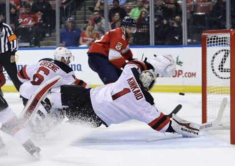 New Jersey Devils goaltender Keith Kinkaid (1) stops the puck as Florida Panthers defenseman Aaron Ekblad (5) looks on during the first period of an NHL hockey game, Monday, Nov. 26, 2018, in Sunrise, Fla.