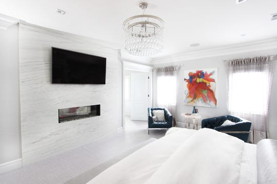 This Livingston master bedroom by DRP Interiors in Franklin Lakes features a custom double-sided fireplace that can also be seen in the master bedroom office.