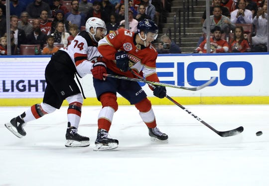 Florida Panthers left wing Dryden Hunt (73) takes a shot on goal as New Jersey Devils defenseman Egor Yakovlev defends during the second period of an NHL hockey game, Monday, Nov. 26, 2018, in Sunrise, Fla.