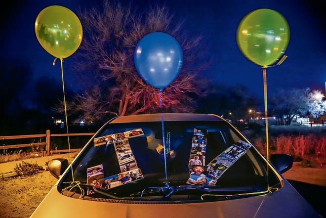 A collage made of photographs of Jeremiah Valencia decorate the hood of a car at the candlelight vigil in remembrance of Jeremiah at Frenchy's Park in Santa Fe on November 26, 2018.