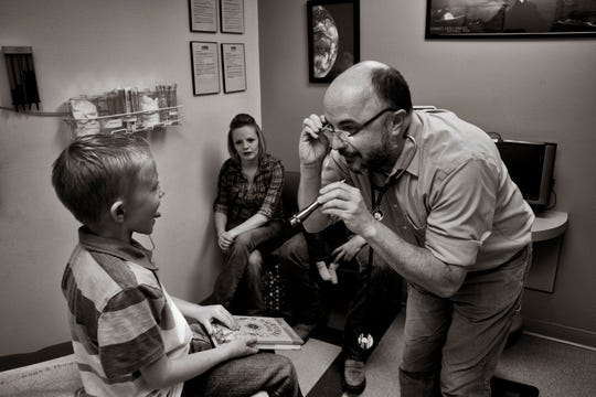 Dr. Brian Etheridge of Silver City performs a well-child visit on a young patient.