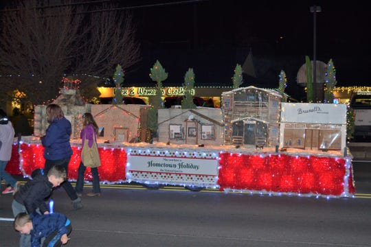 The Festival of Lights parade finds children scattering around collecting candy as the illuminated floats move down Sudderth Drive bring joy and holiday fun to the Village.