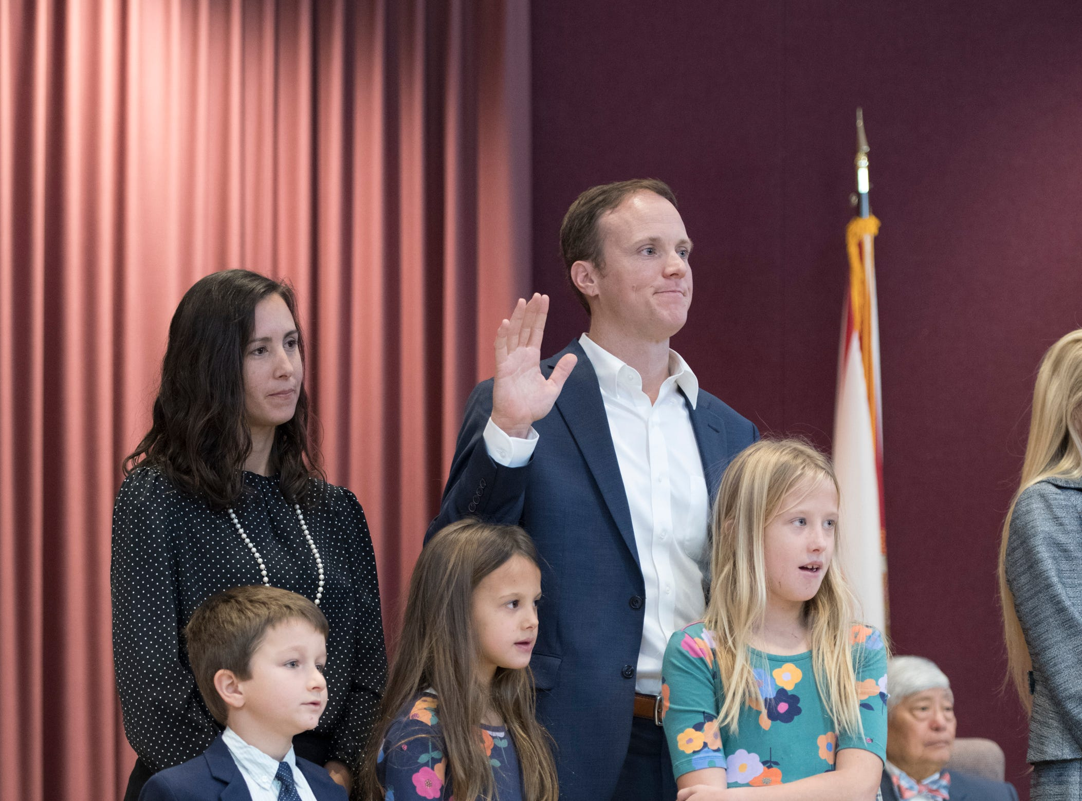 Newly elected council member Jared Moore raises his hand as he is sworn in during the Pensacola City Council installation ceremony at City Hall in Pensacola on Tuesday, November 27, 2018.