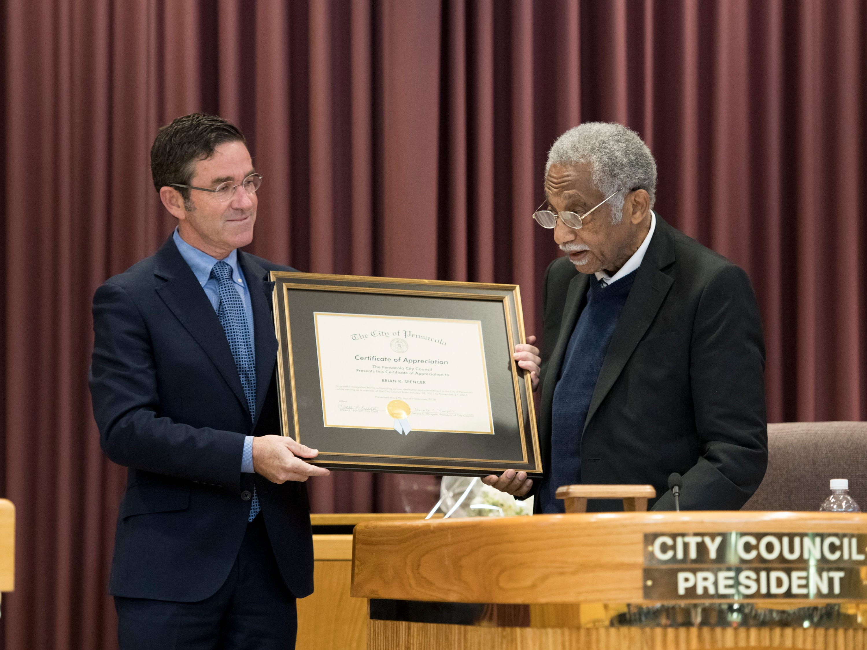 City council president Gerald Wingate, right, presents outgoing council member Brian Spencer a certificate of appreciation prior to the Pensacola City Council and Mayor installation ceremony at City Hall in Pensacola on Tuesday, November 27, 2018.