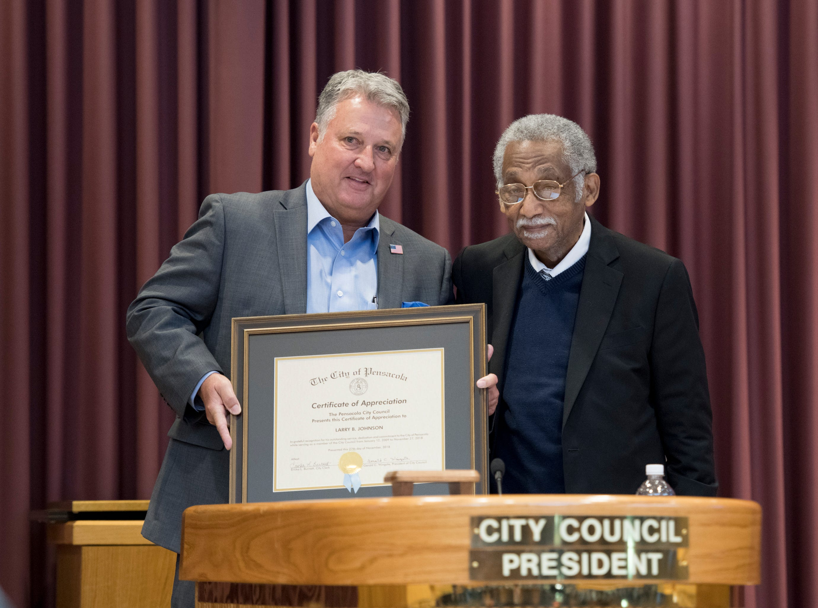 City council president Gerald Wingate, right, presents outgoing council member Larry Johnson a certificate of appreciation prior to the Pensacola City Council and Mayor installation ceremony at City Hall in Pensacola on Tuesday, November 27, 2018.