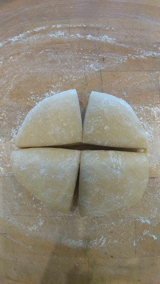 Dough is kneaded, rested and cut into quarters.