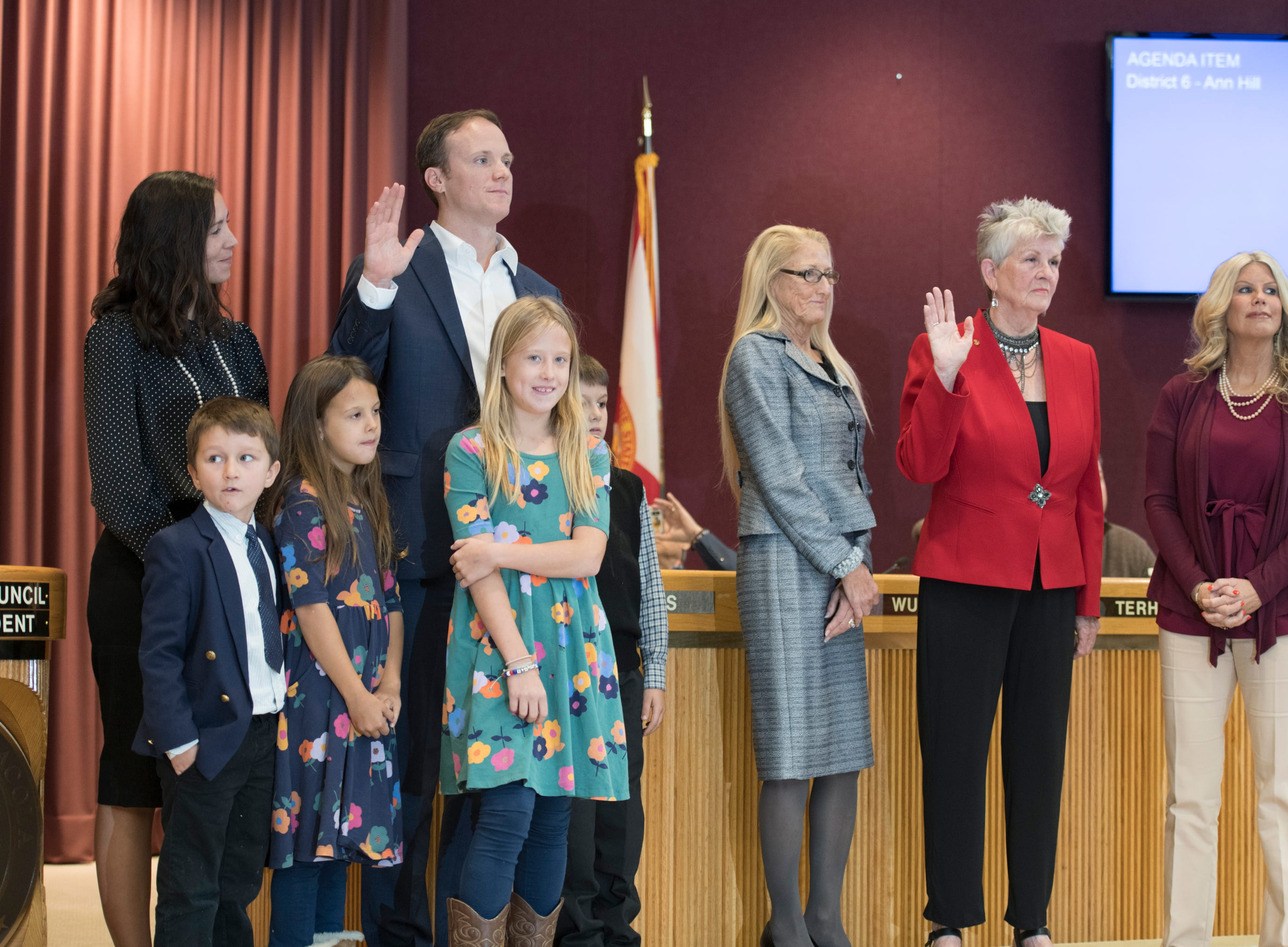 Newly elected council members Jared Moore, left, and Sherri Myers raise their hands as they are sworn in during the Pensacola City Council installation ceremony at City Hall in Pensacola on Tuesday, November 27, 2018.