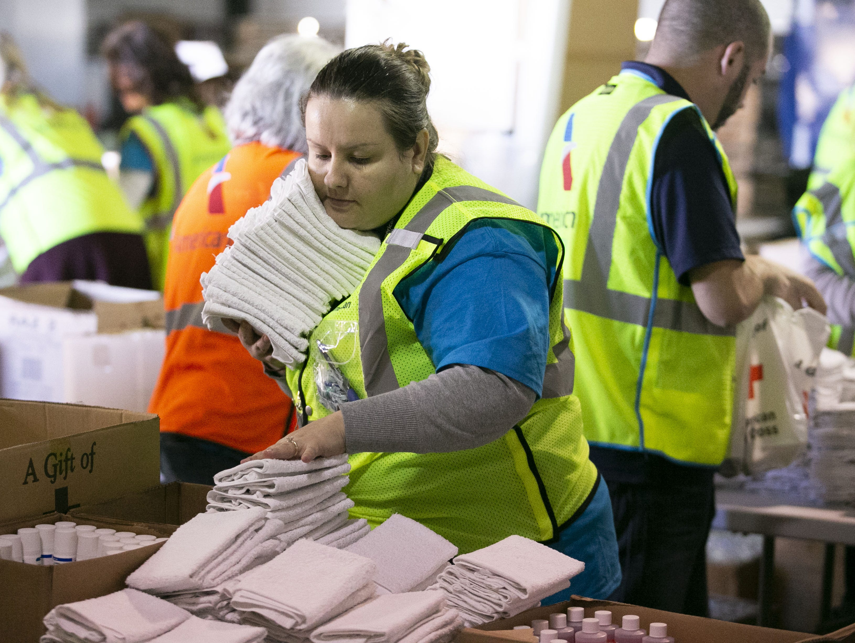 American Airlines employees Svetlana Dzhurova Mitova stacks wash clothes while packaging amenity kits for the victims of the California wildfires, at the American Airlines cargo facility in Phoenix on Tuesday, Nov. 27, 2018.