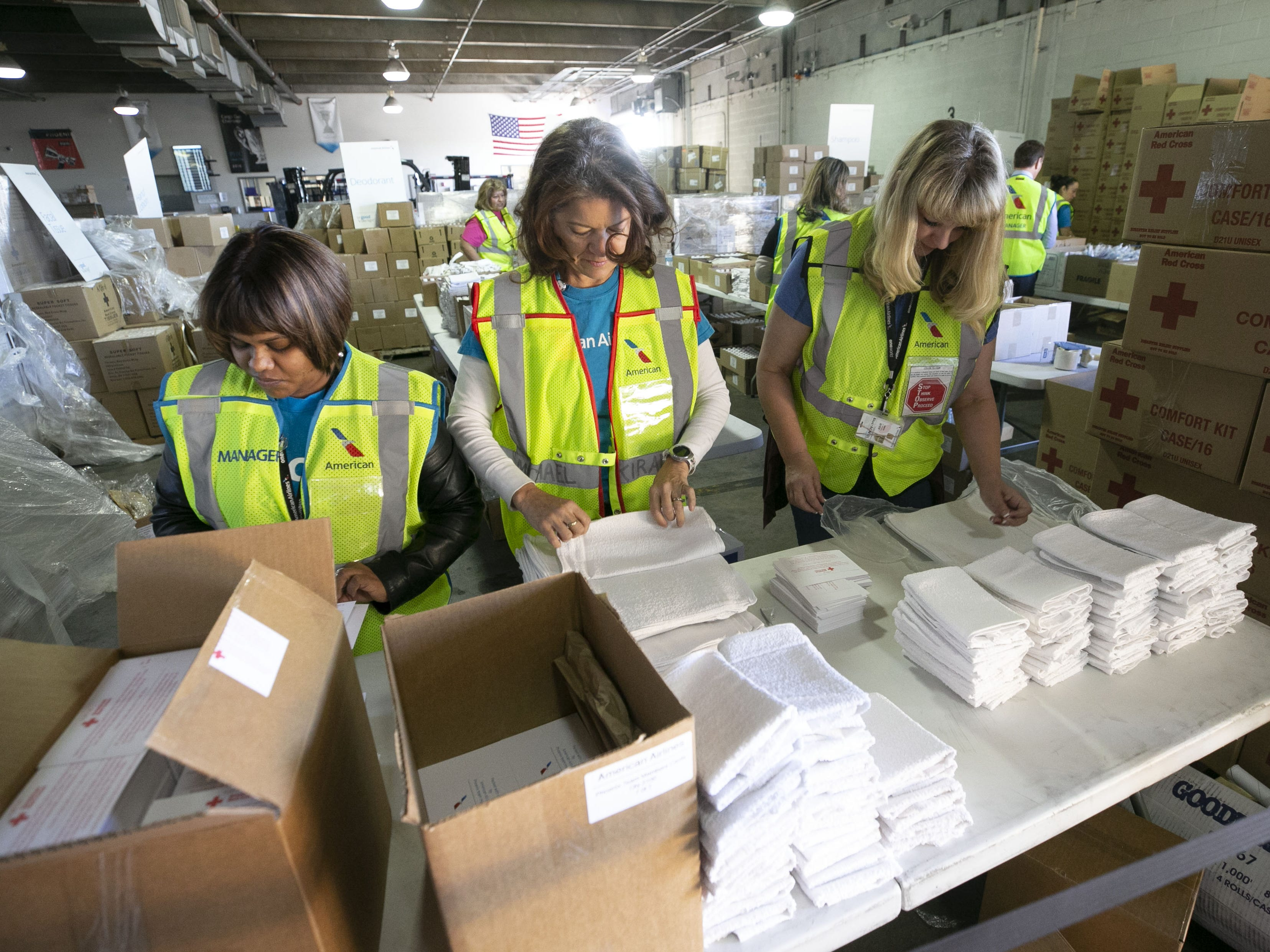 American Airlines employees (from left) Mahbuba Aktar, Carmen Arias-McKinn and Julie Howard, stack wash clothes while packaging amenity kits for the victims of the California wildfires, at the American Airlines cargo facility in Phoenix on Tuesday, Nov. 27, 2018.