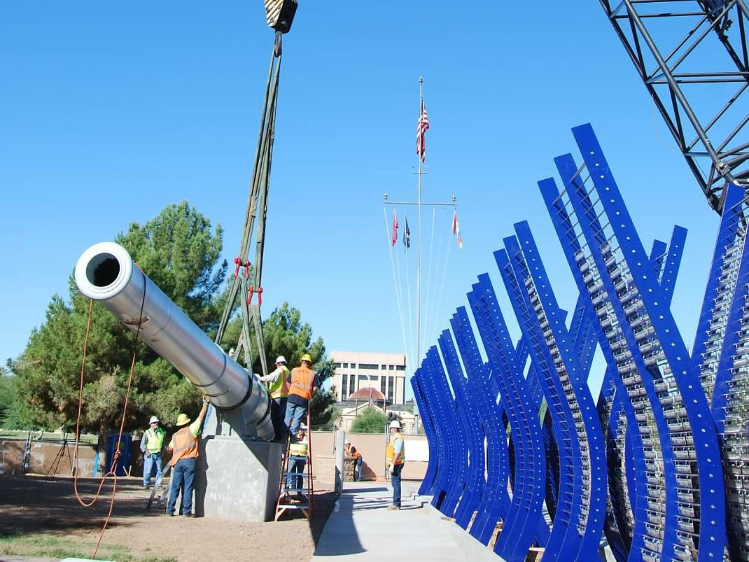 A crane sets a battleship gun at the World War II memorial. The memorial at Wesley Bolin Memorial Plaza at the Arizona State Capitol, was  dedicated in 2013 and honors Pearl Harbor service members and World War II veterans.