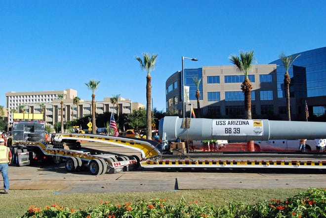 A truck hauls the USS Arizona's 14-inch gun at the memorial at Wesley Bolin Memorial Plaza at the Arizona State Capitol. The memorial was  dedicated in 2013 and honors Pearl Harbor service members and World War II veterans.