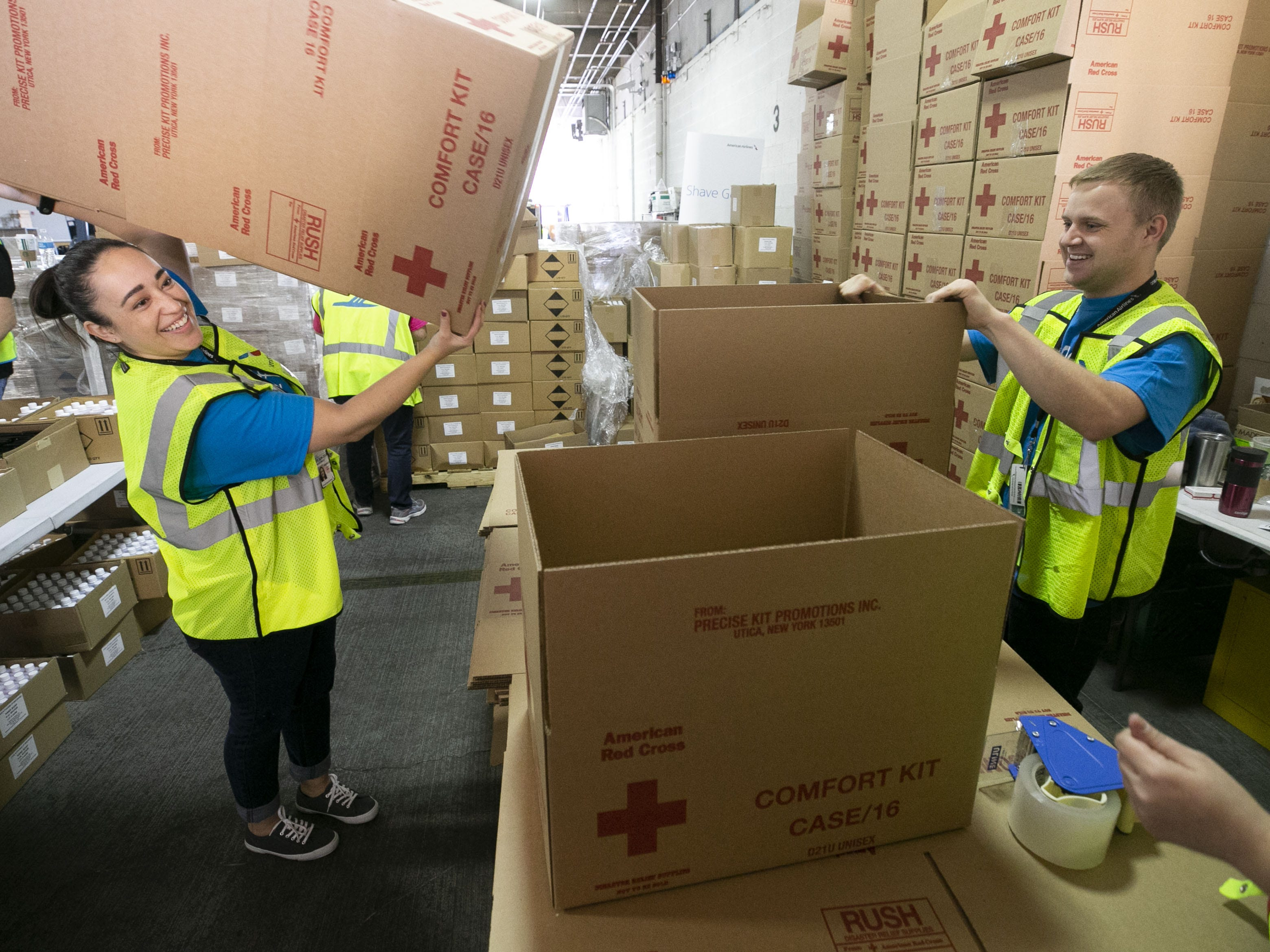 American Airlines employees Danielle Padilla (left) and Caleb Stevens fold boxes for amenity kits for the victims of the California wildfires, at the American Airlines cargo facility in Phoenix on Tuesday, Nov. 27, 2018.