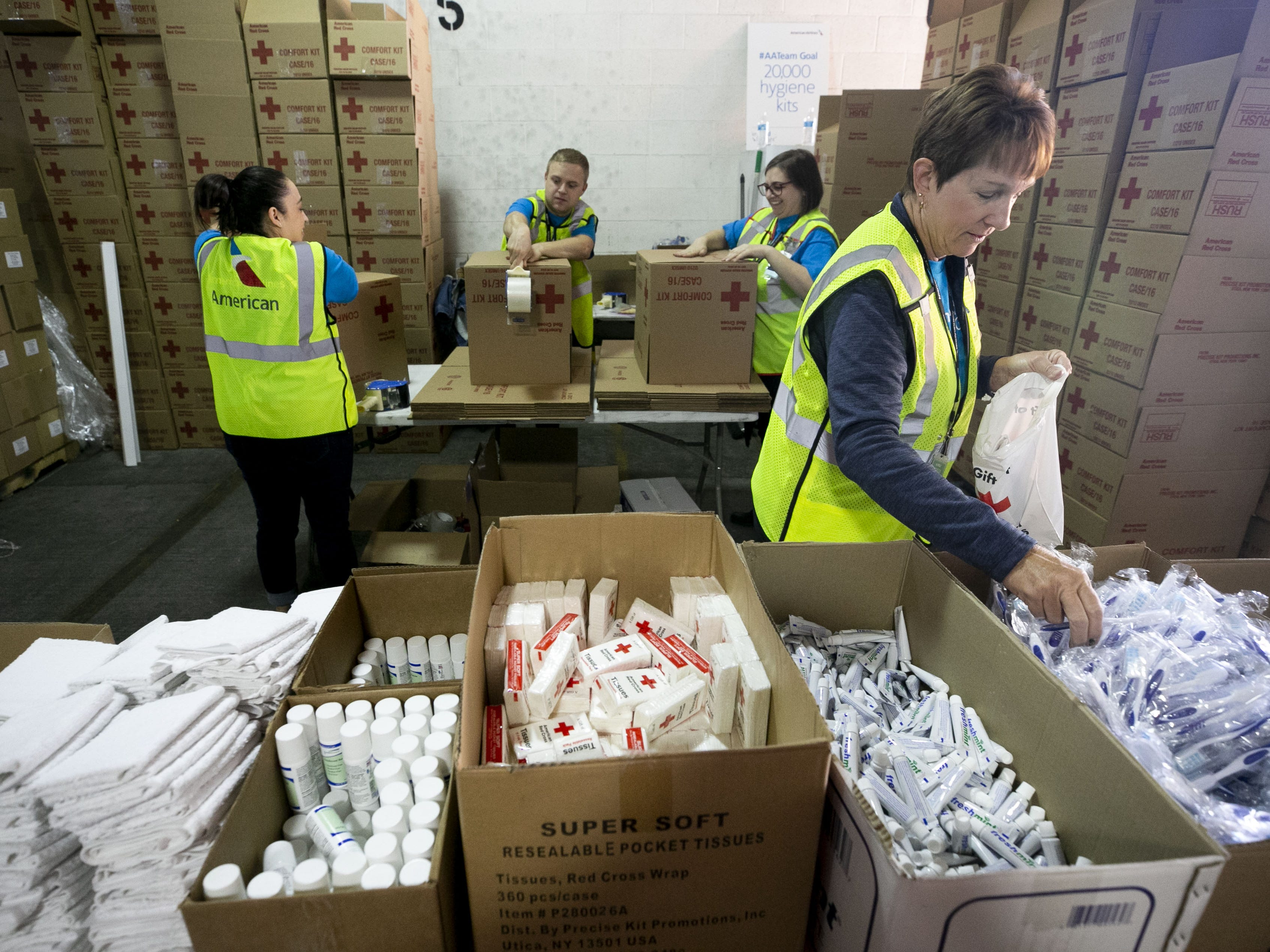 American Airlines employee Lore Taylor packages amenity kits for the victims of the California wildfires, at the American Airlines cargo facility in Phoenix on Tuesday, Nov. 27, 2018.