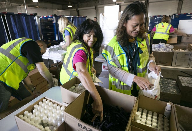 American Airlines employees Mary Ann Pizzinato (left) and Mary Joy Toribiong package amenity kits for the victims of the California wildfires, at the American Airlines cargo facility in Phoenix on Tuesday, Nov. 27, 2018.