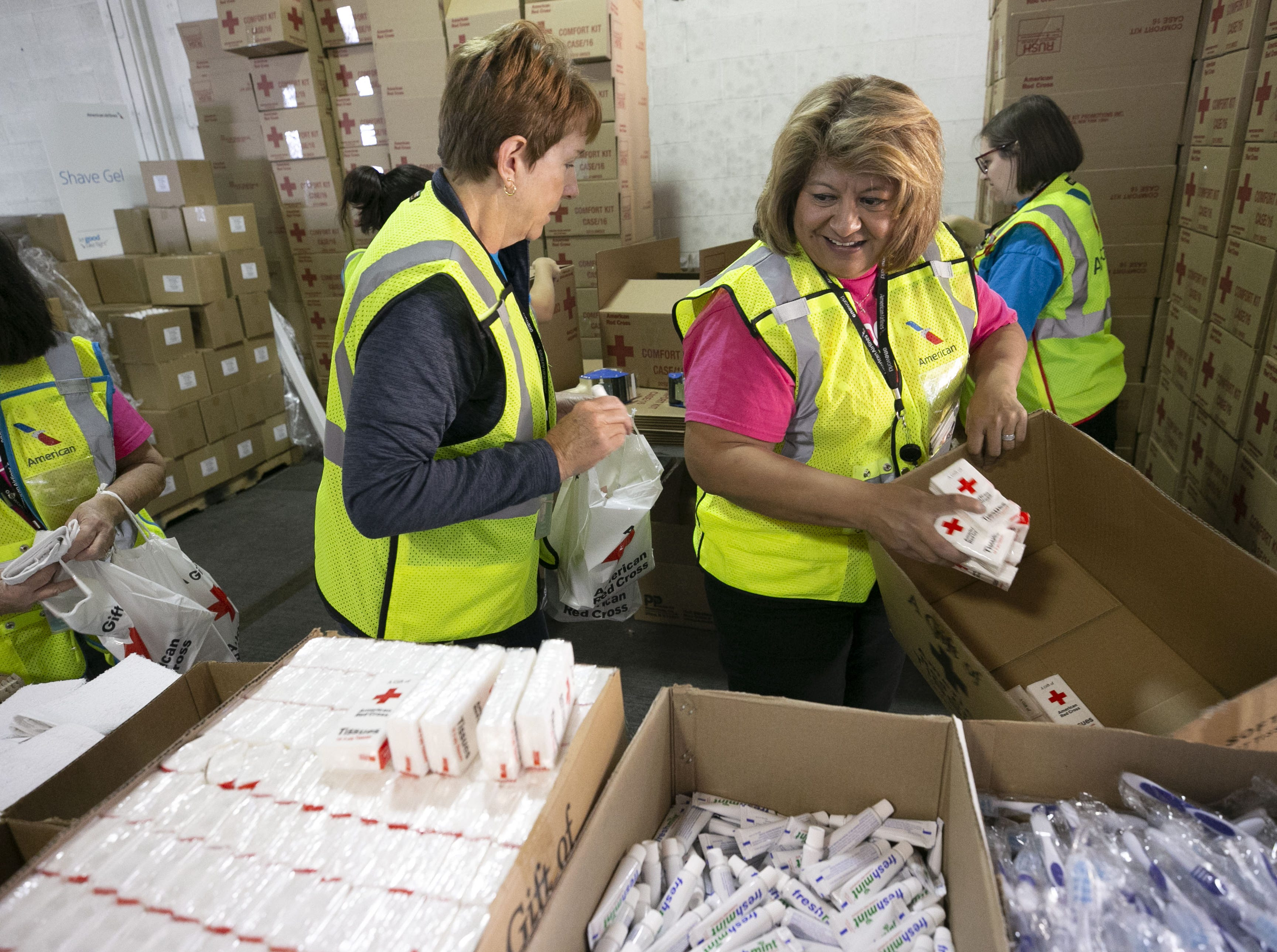 American Airlines employees Lore Taylor (left) and Maria Castro package amenity kits for the victims of the California wildfires, at the American Airlines cargo facility in Phoenix on Tuesday, Nov. 27, 2018.