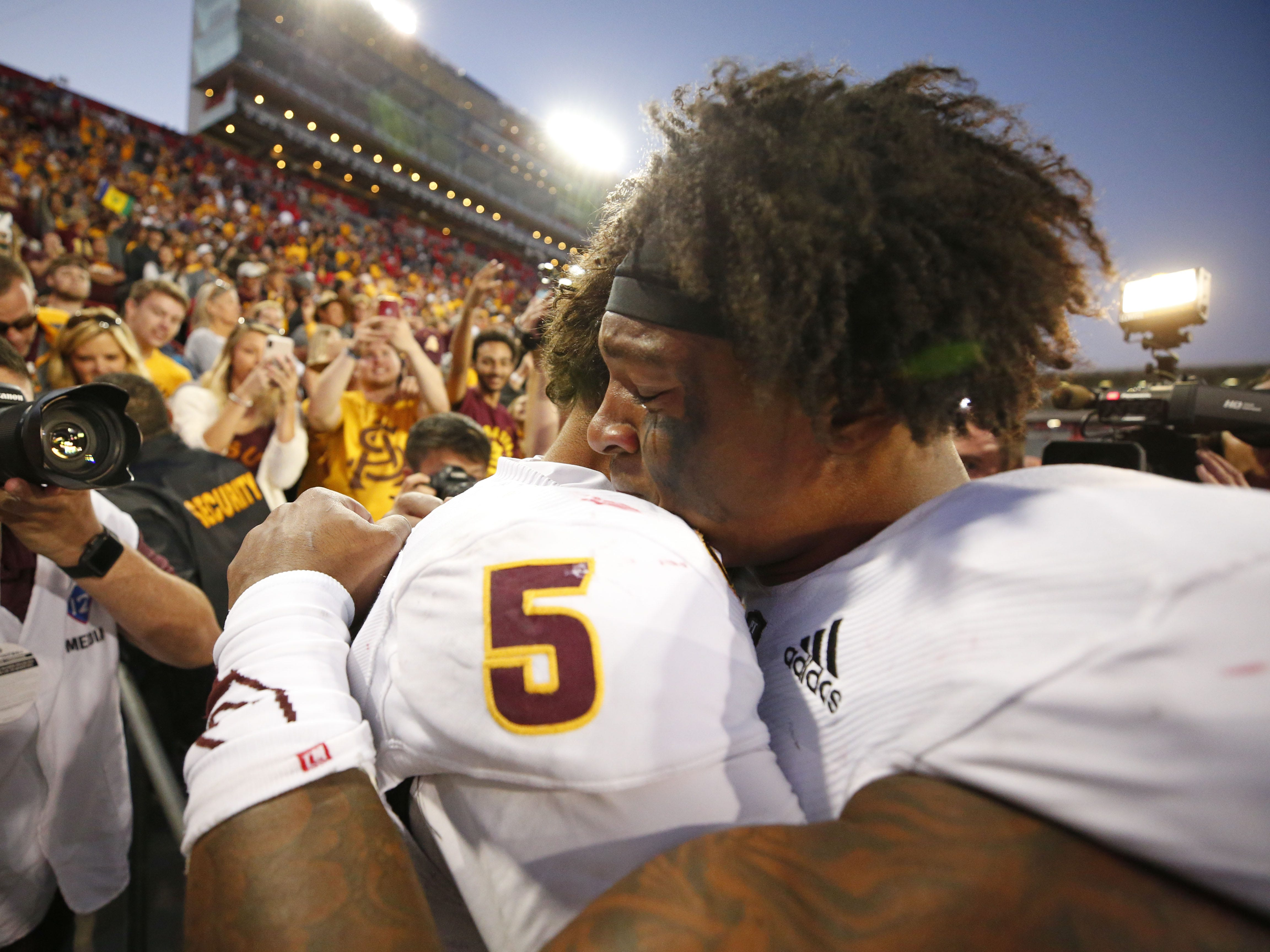 Arizona State Sun Devils quarterback Manny Wilkins (5) and Arizona State Sun Devils wide receiver N'Keal Harry (1) have an emotional moment after winning the Territorial Cup football game against the Arizona Wildcats at Arizona Stadium in Tucson on November 24.