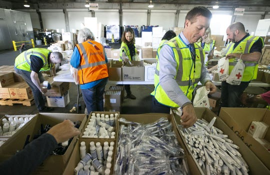 American Airlines employees Tim James packages amenity kits for the victims of the California wildfires, at the American Airlines cargo facility in Phoenix on Tuesday, Nov. 27, 2018.
