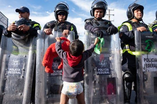 Un pequeño niño migrante intenta jugar con los policías.