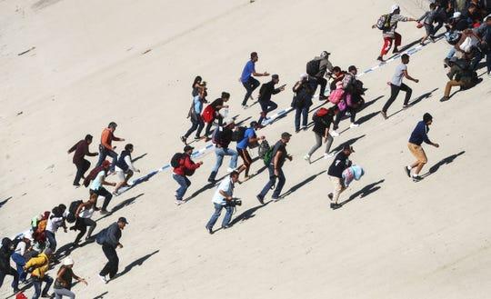 Un grupo de migrantes trepan por las paredes de un río seco en un intento de evadir a los policías que custodian la entrada a EEUU.