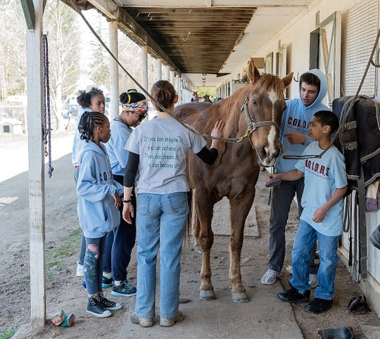 Poughkeepsie middle and high school students who are members of C.O.L.O.R.S. volunteer at the Southern Dutchess Equestrian Center in 2018.
