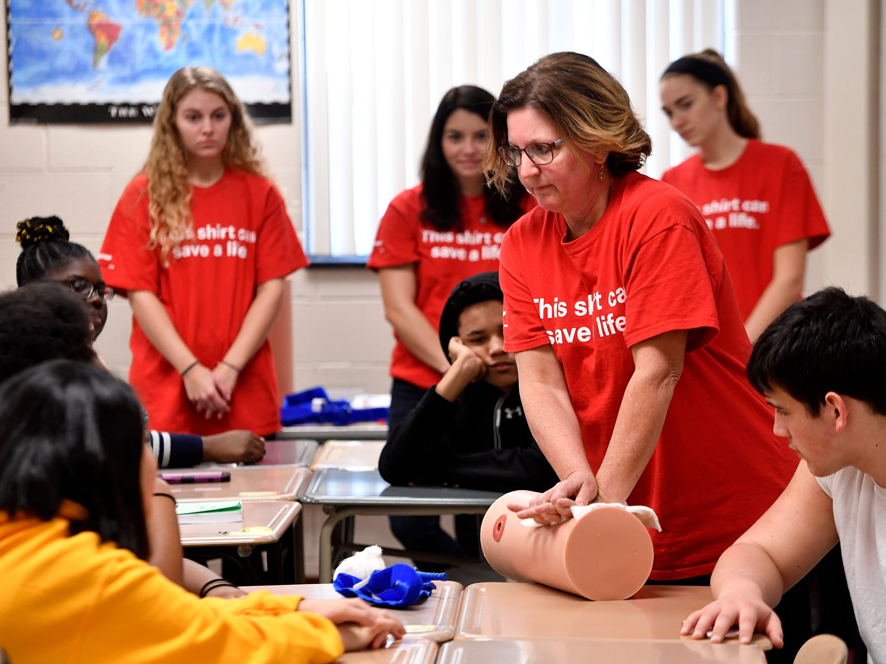 Kelli Masters, assistant professor of nursing at York College, demonstrates the proper way to apply pressure to a bleeding wound for students in the William Penn Senior High School Public Safety and Emergency Services class, Tuesday, Nov. 27, 2018.  John A. Pavoncello photo
