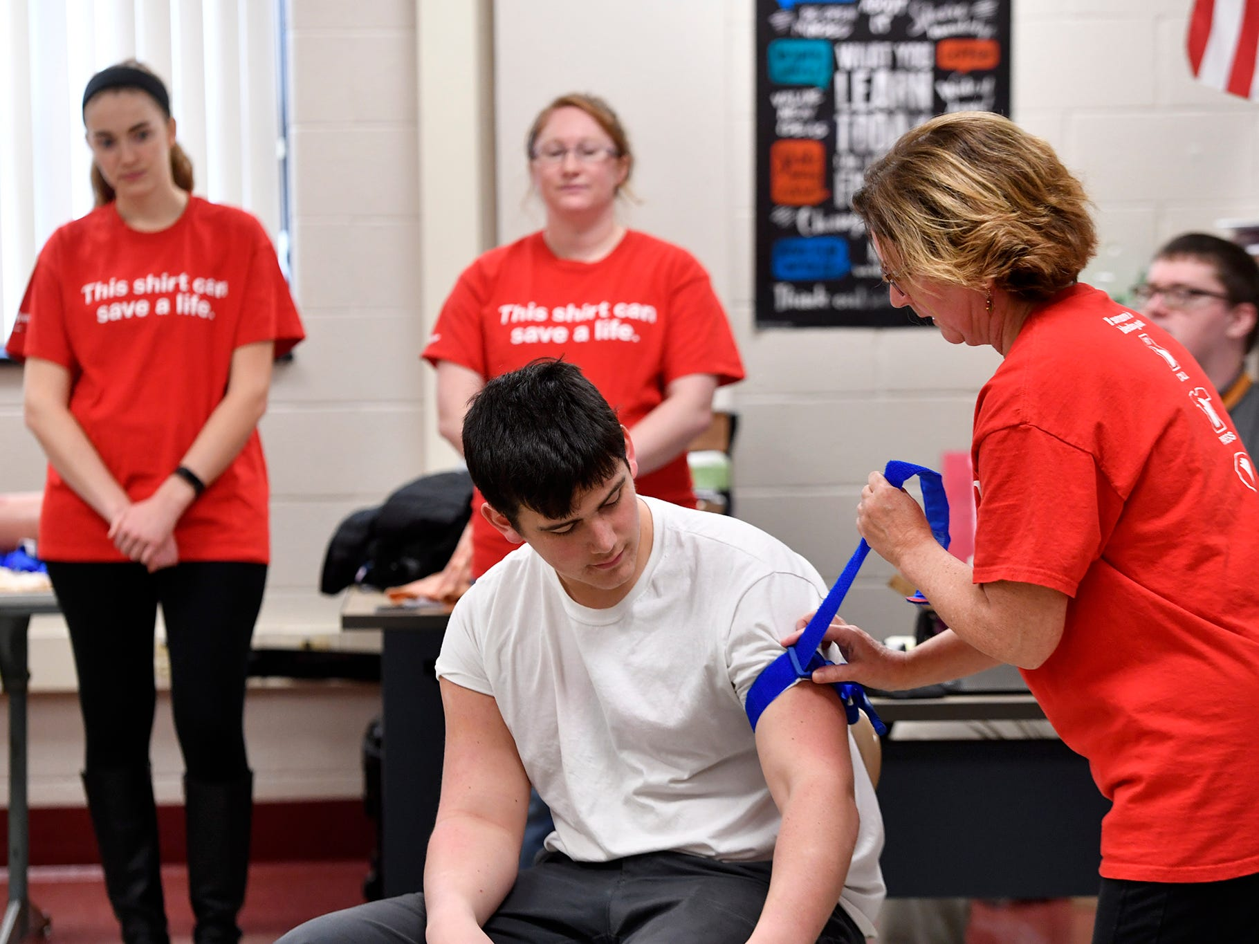 Kelli Masters, assistant professor of nursing at York College, demonstrates the proper way to apply a tourniquet on Trey Bernstein, 16 , for students in the William Penn Senior High School Public Safety and Emergency Services class, Tuesday, November 27, 2018. John A. Pavoncello photo