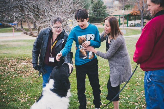 Autism Anchor Dogs founder Kirsten Becker, 15-year-old Ethan Earl and his mom Debbie Earl meet Mack, a service dog.