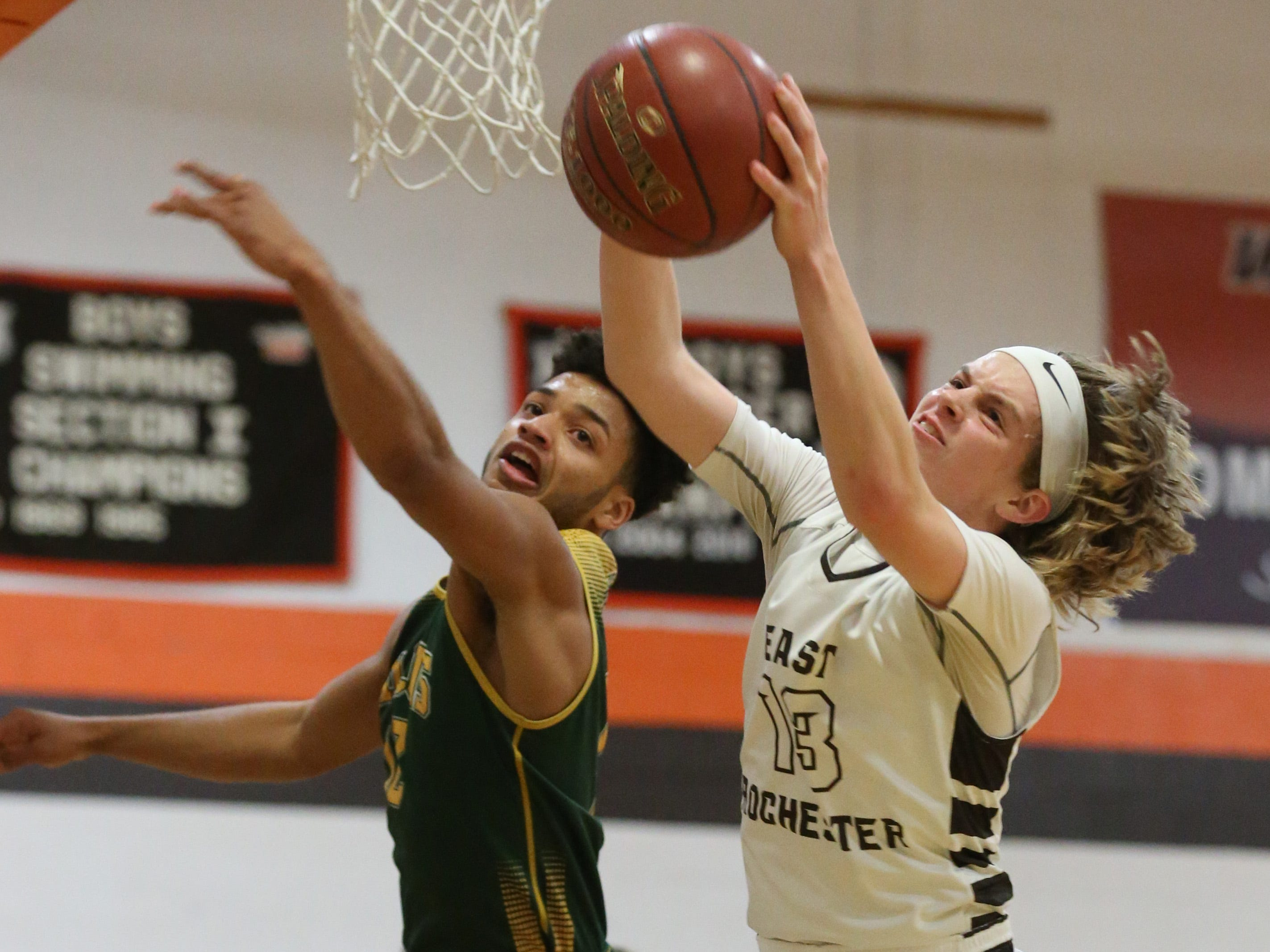 East Rochester's Austin Mack, right, pulls down a rebound away from Finney's Xavier Smith.