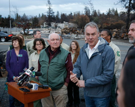 Interior Secretary Ryan Zinke, right, answers a reporters question after touring fire ravaged Paradise, Calif. with Agriculture Secretary Sonny Perdue, center, Monday, Nov. 26, 2018. The pair advocated more aggressive forest management policies to mitigate damage from future wildfires. (AP Photo/Rich Pedroncelli)