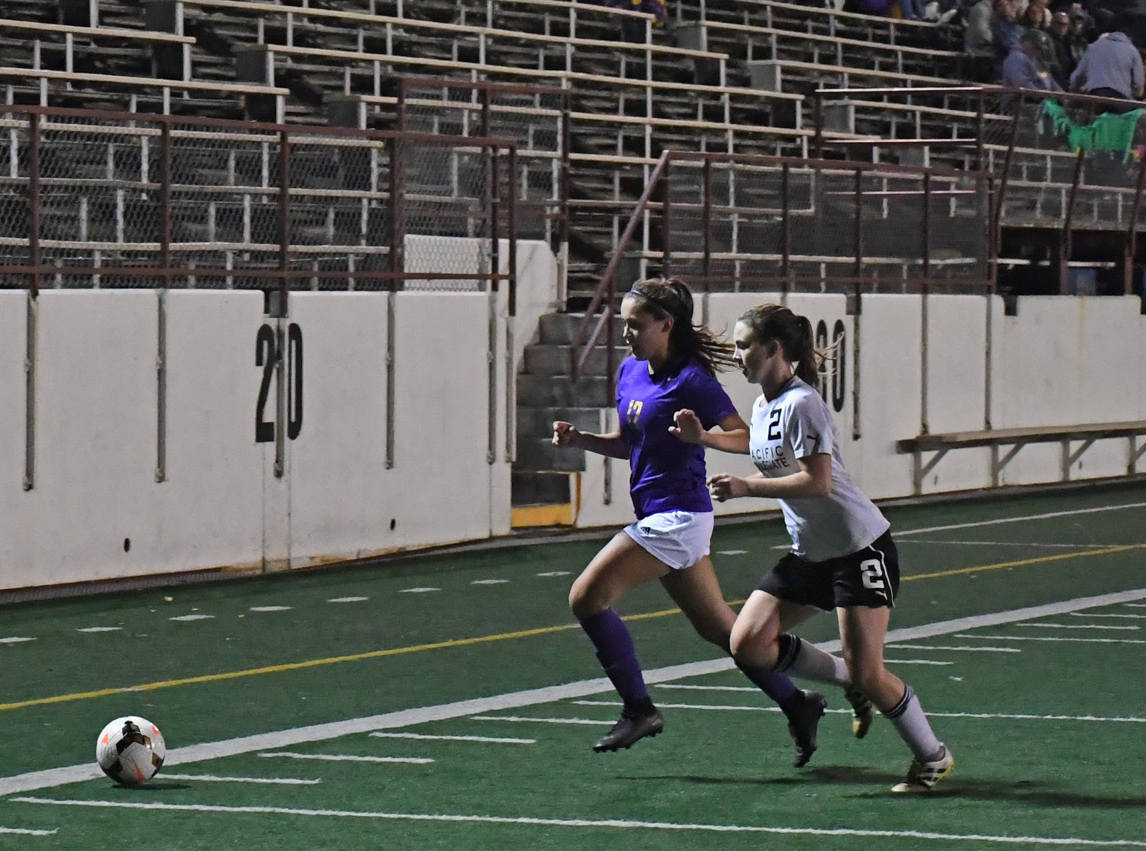 Junior Victoria Pelagio (12) fights for possession along the sideline.