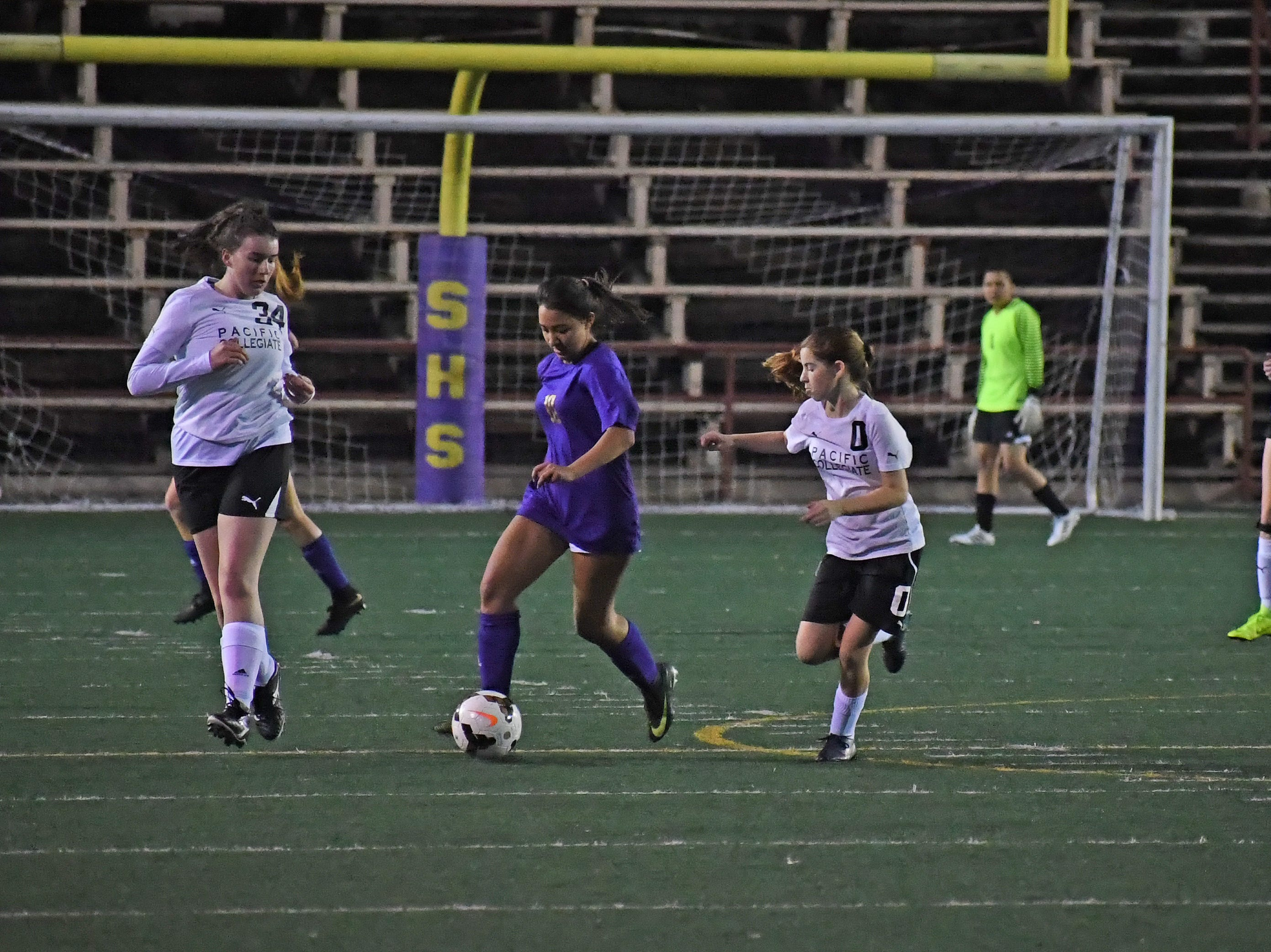 Senior Yadira Acosta (10) dribbles past midfield.