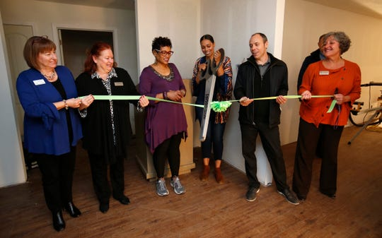 Christina Ford, center, cuts the ribbon with her mom, Marda Jackson, officials from Community Partnership of the Ozarks, and Harmony House for Marda's House, a transitional home for domestic violence victims, on Tuesday, Nov. 27, 2018.