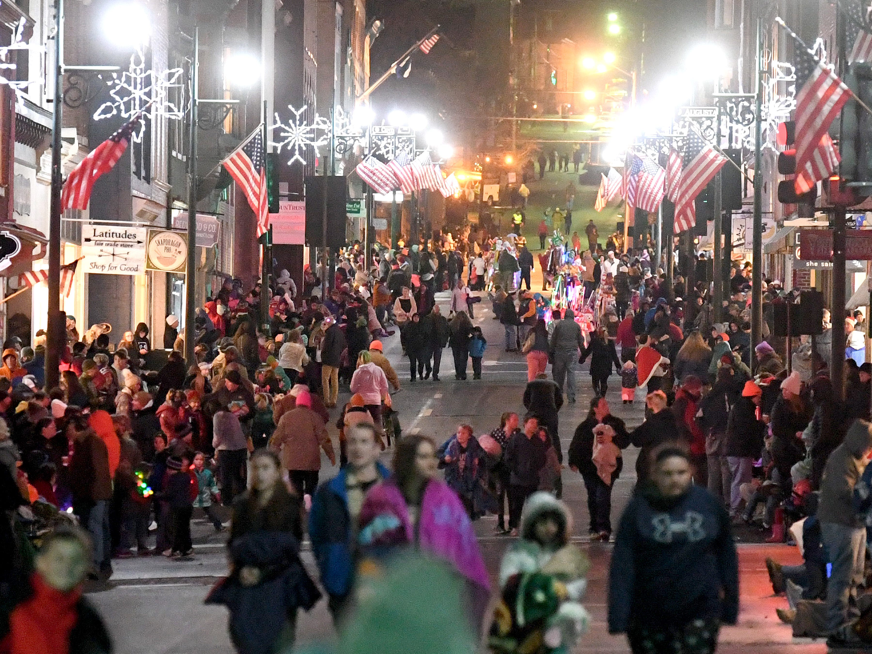 People walk along Beverley Street as they wait for the start of the Staunton Christmas Parade in downtown on Monday, Nov. 26, 2018.