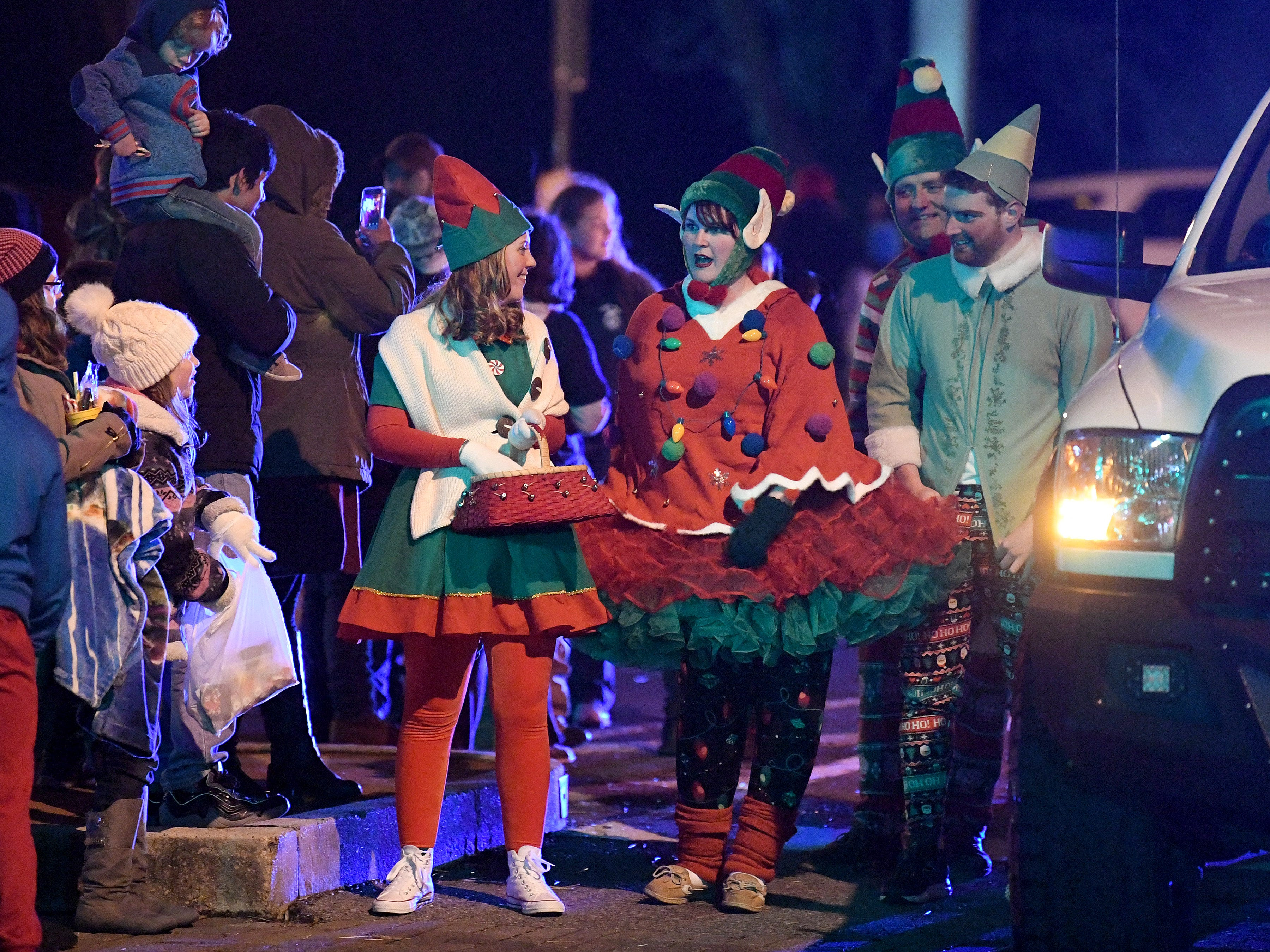 One of the elves (middle) walking alongside Santa's float starts performing the floss dance during the Staunton Christmas Parade makes its way through downtown on Monday, Nov. 26, 2018.