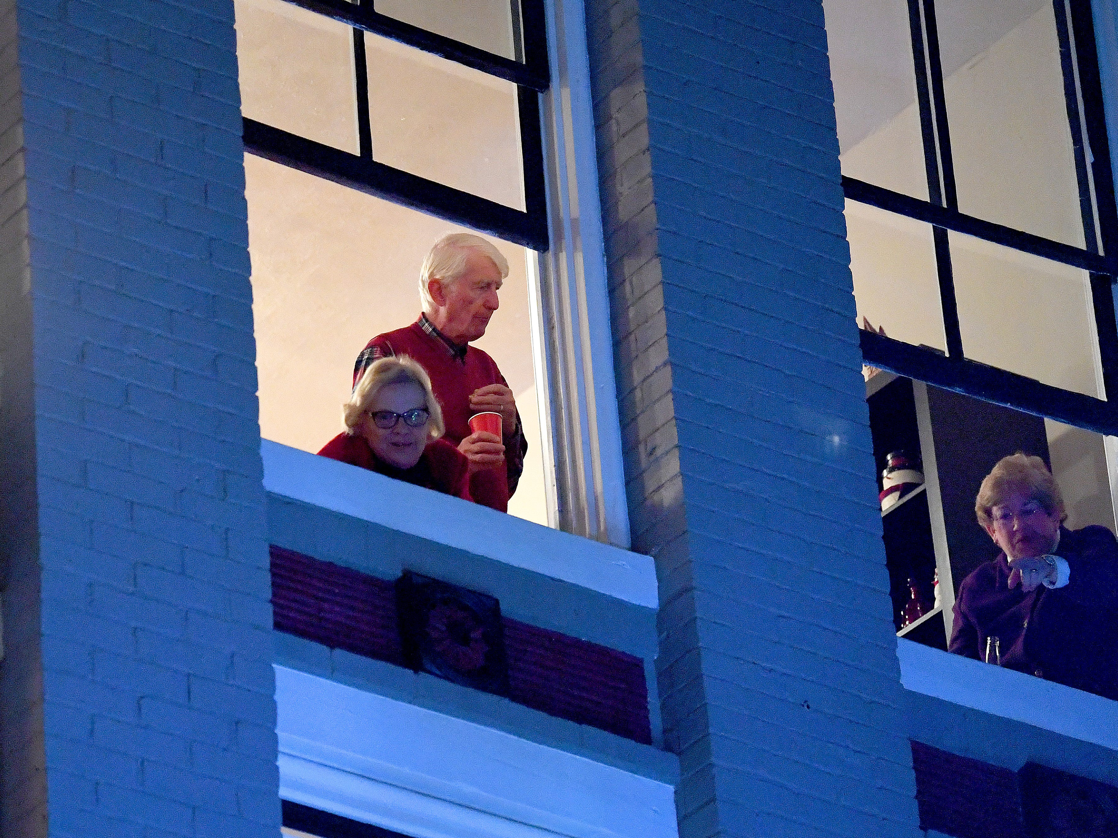Spectators watch the Staunton Christmas Parade from a second floor vantage point overlooking the parade route on West Beverley Street on Monday, Nov. 26, 2018.
