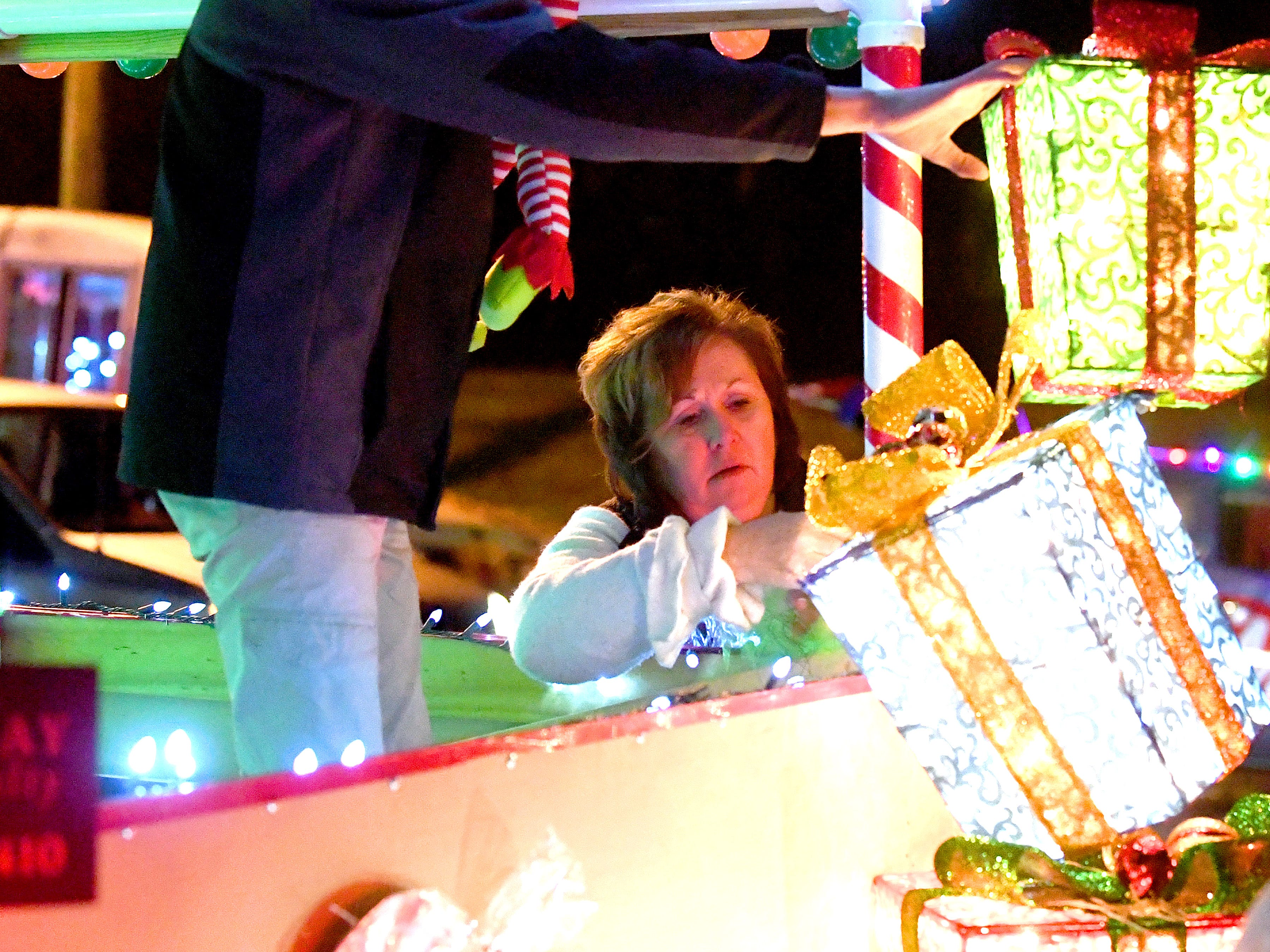 Karen Carpenter of Kline May Realty helps decorate their float before the start of the Staunton Christmas Parade on Monday, Nov. 26, 2018.