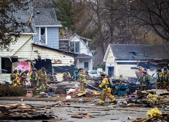 St. Paul firefighters work at the scene of a house explosion in St. Paul, Minn., on Friday, Nov. 23.