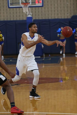 TCC's Richard Washington passes the ball from the top of the key against the Combine Academy Warriors.