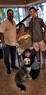Robert and Lourdes Wydra and sons AJ and Logan, with Uno in a family picture.