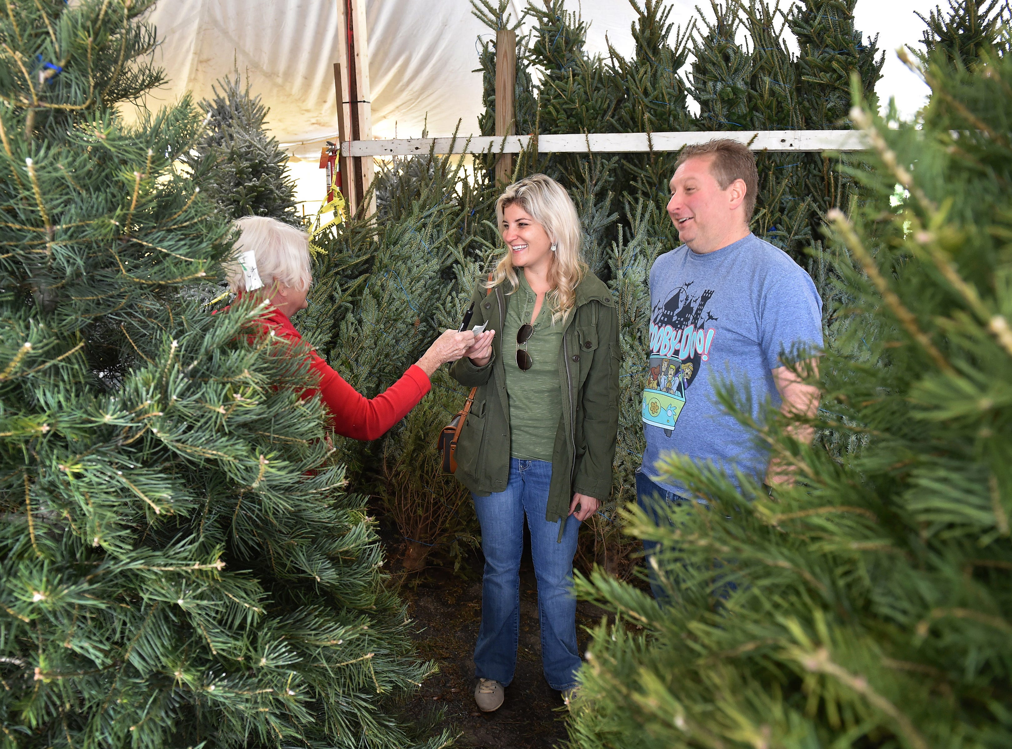 "Caroline Smith (center) and her boyfriend Robert Meitzer pick out the perfect Fraser Fir Christmas tree from Brenda Hodge, owner of Hodge Podge Trees at the Kmart Plaza parking lot in the 1600 block of US 1 on Tuesday, Nov. 27, 2018, in Vero Beach. ""First Christmas Tree, bought it together, looking forward to decorating it with some schnapps and a hot chocolate,"" Meitzer said. The couple from Vero Beach picked out their first Christmas tree together on their day off work as cooler temperatures from a weather front moved south across the Treasure Coast."
