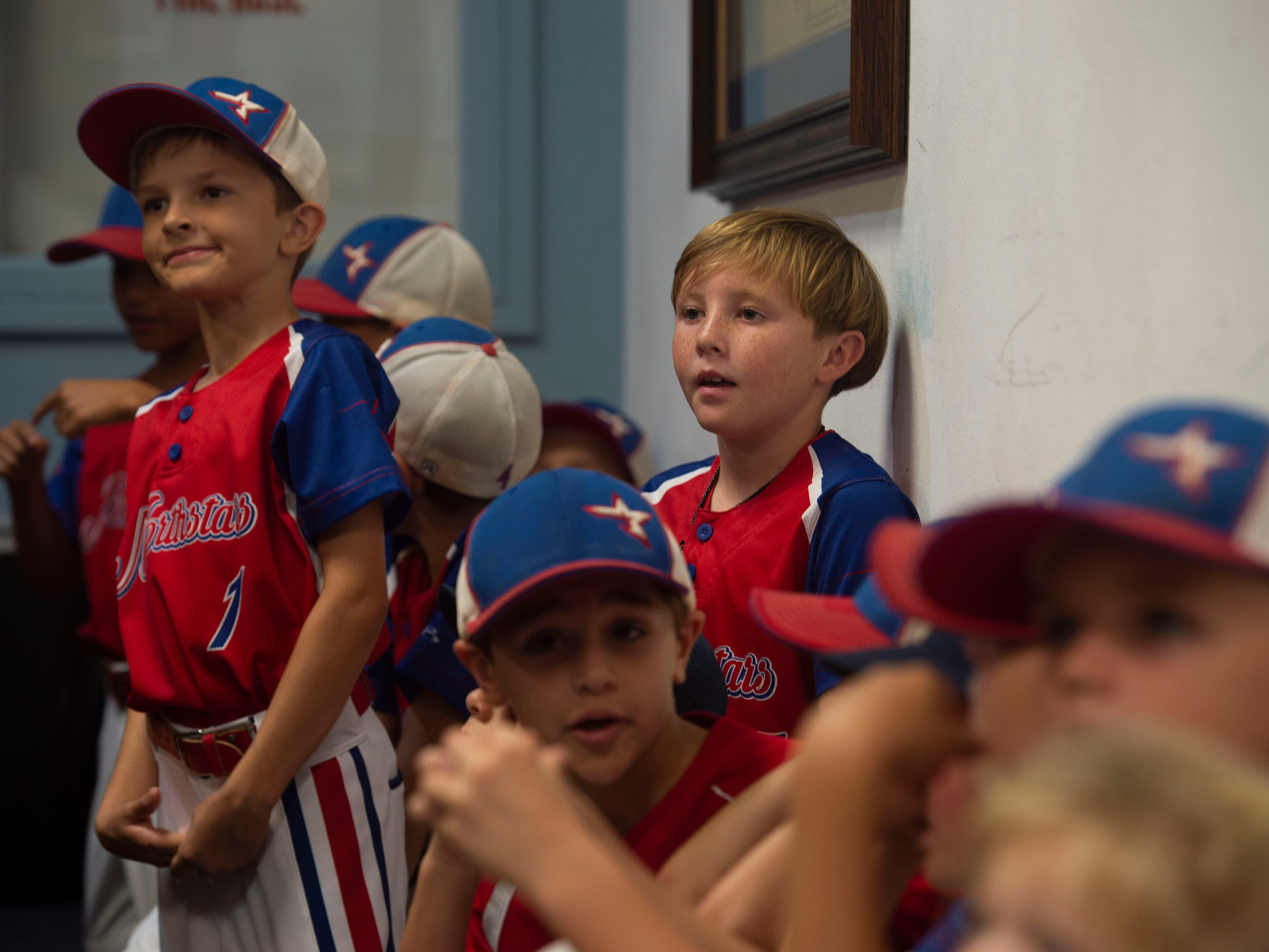Surrounded by teammates, Northstars player Colby Galinis (center,) 9, of SewallÕs Point, looks on in curiosity ahead of his first public meeting Monday, Nov. 26, 2018 at Stuart City Hall. The city commission meeting was packed full of young baseball players and their parents opposing the redevelopment of Sailfish Park and its baseball fields.