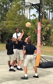 Landau Eugene MurphyJr. shoots hoops  with Samaritan Center boys Isaac, Tristan, Aiden, Brian and Aiden.