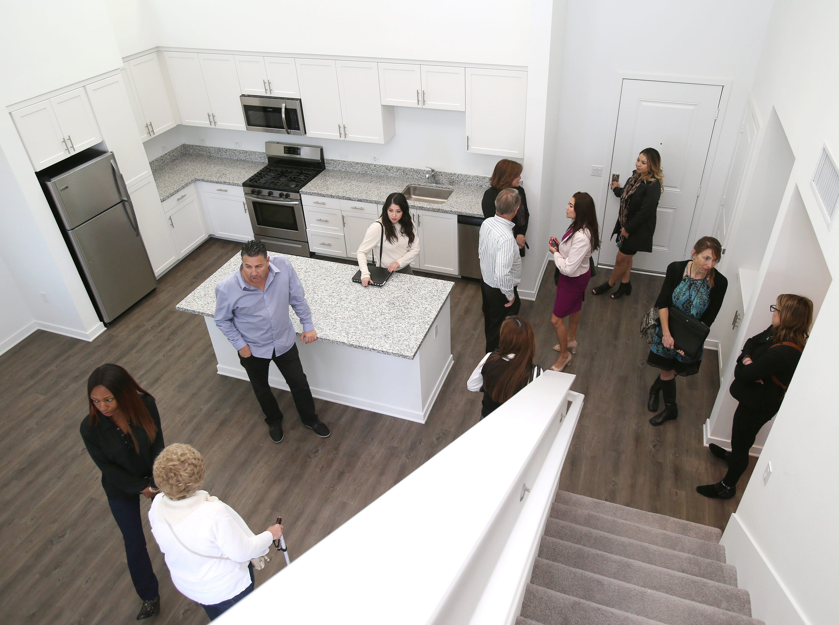 Samantha Martinez, at door, assistant manager for The Junction at the Wagon Wheel, shows guests a one-bedroom plus a loft unit that on the fourth floor of the new apartment complex on Wagon Wheel Road in Oxnard.