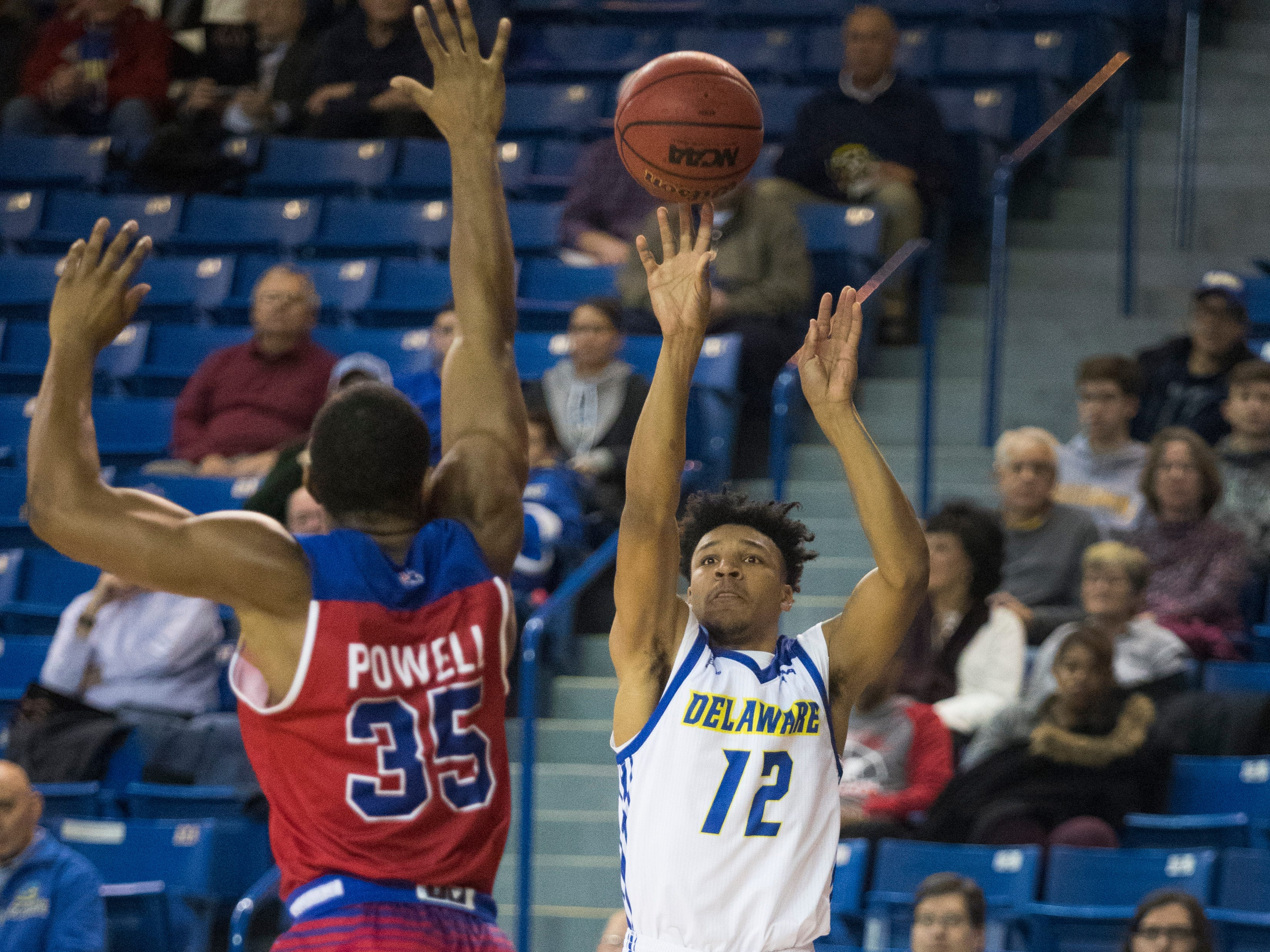 Delaware's Ithiel Horton (12) shoot a three-pointer while being guarded by Louisiana Tech's Oliver Powell (35) Monday at the Bob Carpenter Center. Delaware defeated Louisiana Tech 75-71.