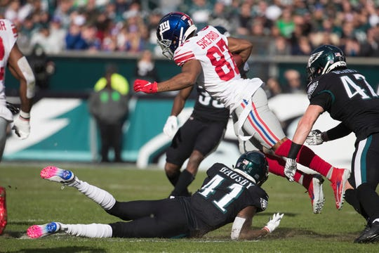 Eagles' De'Vante Bausby (41) trips up New York's Sterling Shepard (87) Sunday at Lincoln Financial Field.