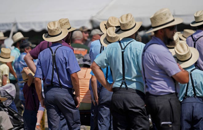 Amish men listen to an auctioneer sell farming equipment at a fundraiser for help pay for families' medical bills.