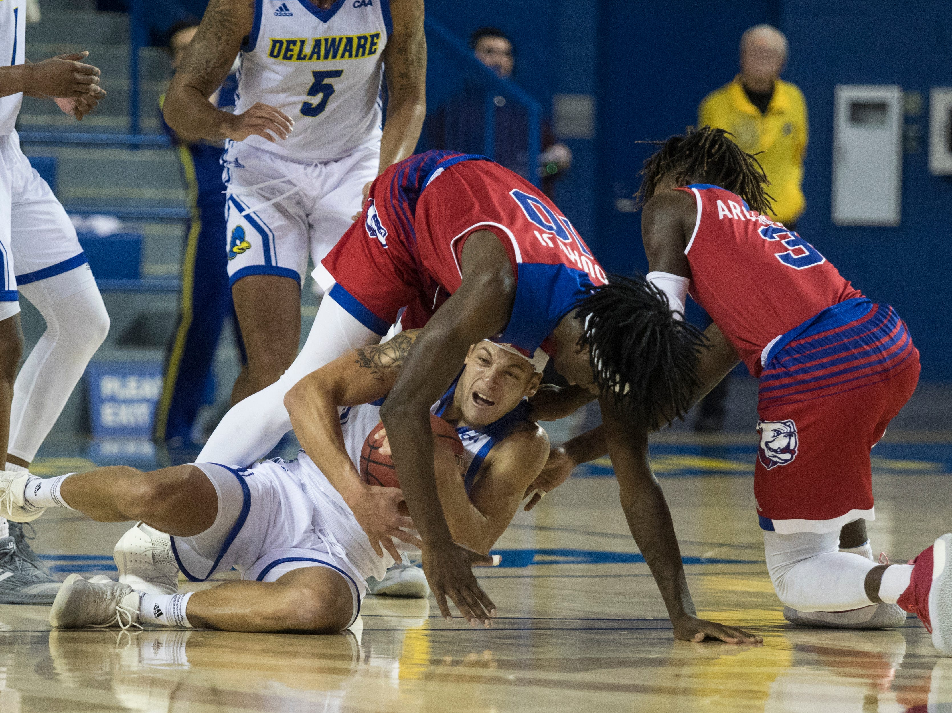 Delaware's Darian Bryant fights for possession against Louisiana Tech's Anthony Duruji (10) and Amorie Archibald (3) Monday at the Bob Carpenter Center. Delaware defeated Louisiana Tech 75-71.
